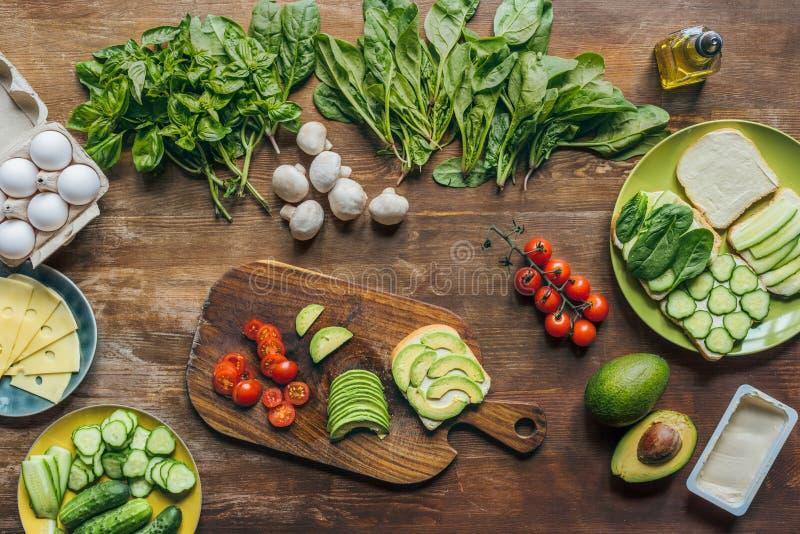 lägenheten lägger med olika ordnade sunda grönsaker, champinjoner och rå fega ägg för att laga mat frukosten arkivbild