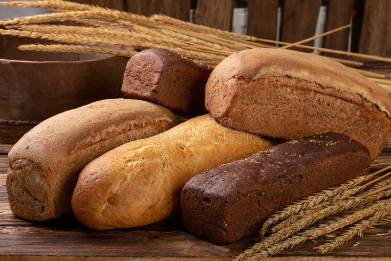 Lägenheten lägger olikt av bröd på träbakgrund med kopieringsutrymme Bageri matbegrepp arkivfoton