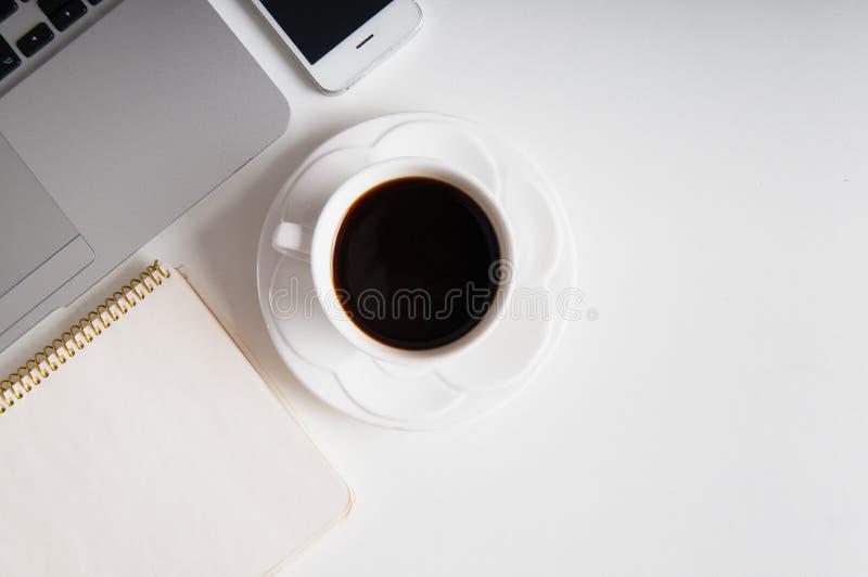 Lägenheten lägger på vit träworkspace med bärbar datordatoren, mobiltelefongrejen och svart kaffe fotografering för bildbyråer