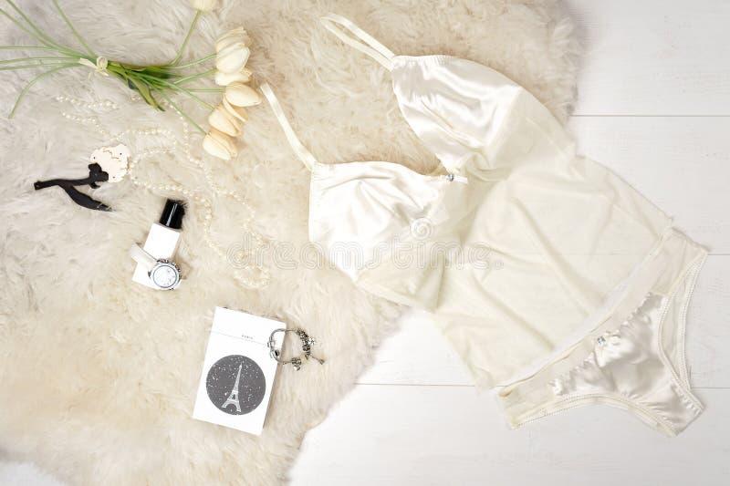 Lägenheten lägger sexig stilfull pastellfärgad beige damunderklädertillbehör och vita tulpan på en vit bakgrund Valentin parti fö fotografering för bildbyråer
