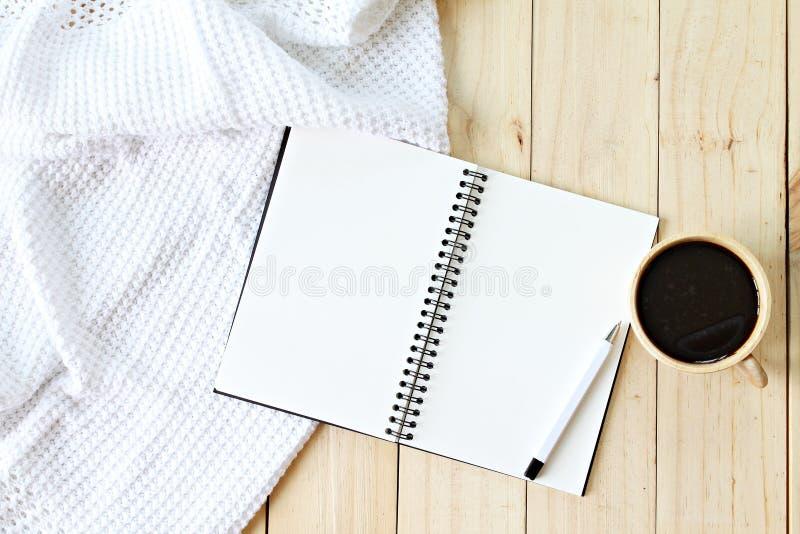 Lägenheten som är lekmanna- av den vit stack filten, koppen kaffe och mellanrumsanteckningsboken skyler över brister på träbakgru royaltyfri fotografi