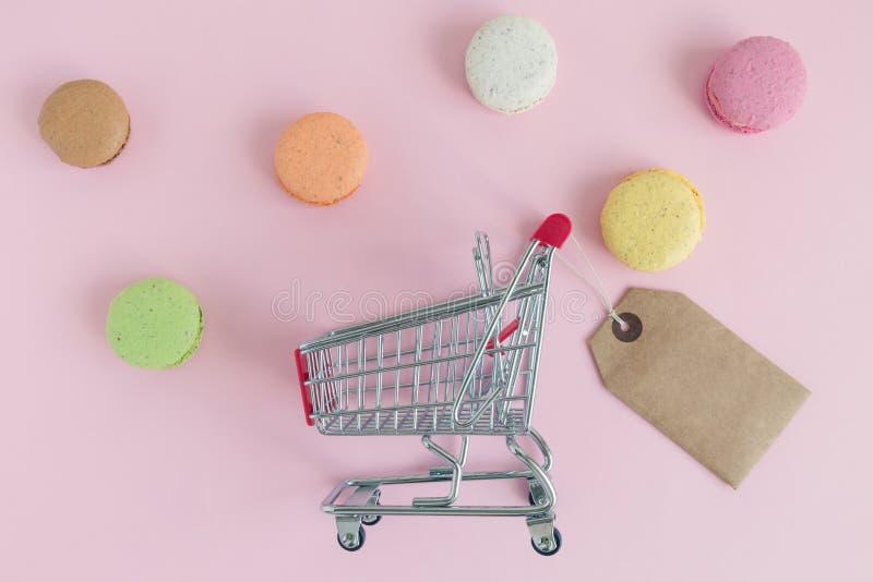 Lägenheten som är lekmanna- av shoppingspårvagnen med etiketten, och mångfärgade macarons gör sammandrag begrepp arkivfoton