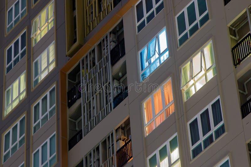 Lägenhetfönster på natten i staden med massor av torn och H royaltyfria bilder
