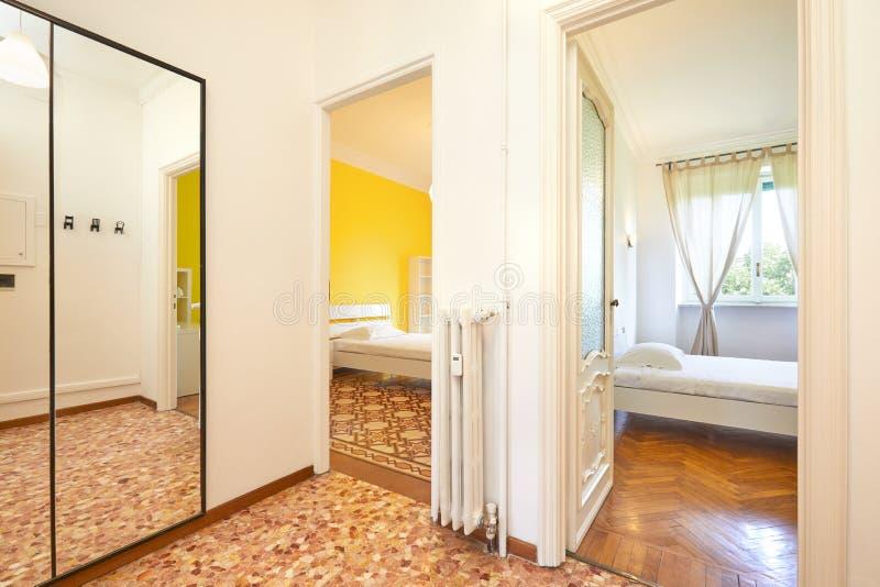 Lägenhetingång och två sovrum i renoverad inre royaltyfri foto