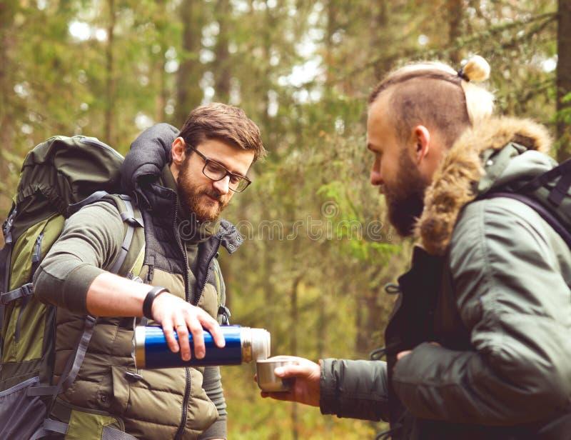 Läger-, affärsföretag-, resande- och kamratskapbegrepp Man med en ryggsäck och ett skägg och hans vän som fotvandrar i skog royaltyfri bild