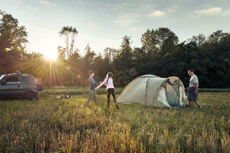 Läger för familjaktiveringstält på solnedgången, härligt sommarlandskap Turism som fotvandrar och reser i natur arkivfoto