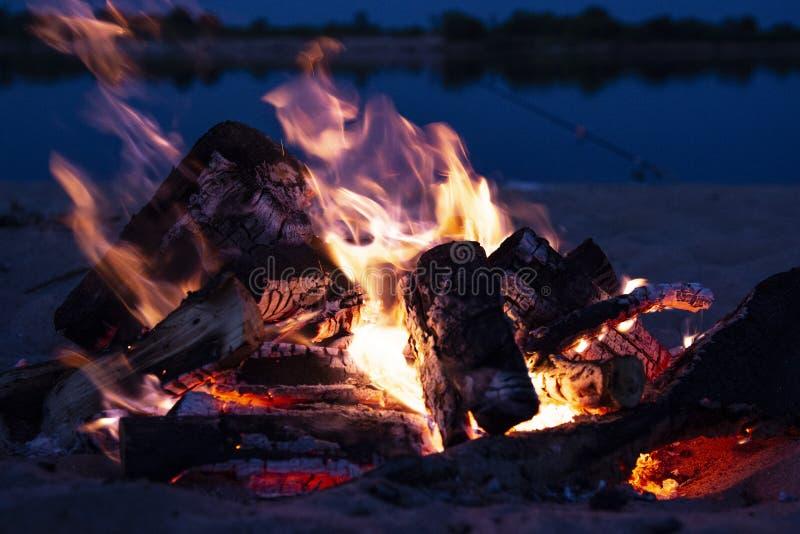 Lägerbrand på natten på floden royaltyfria foton