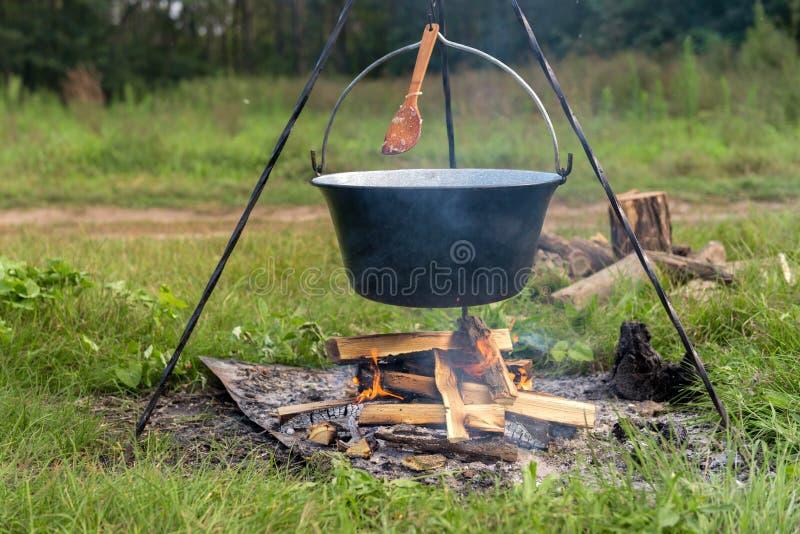 Lägerbrand som bränner utomhus med krukan arkivfoto
