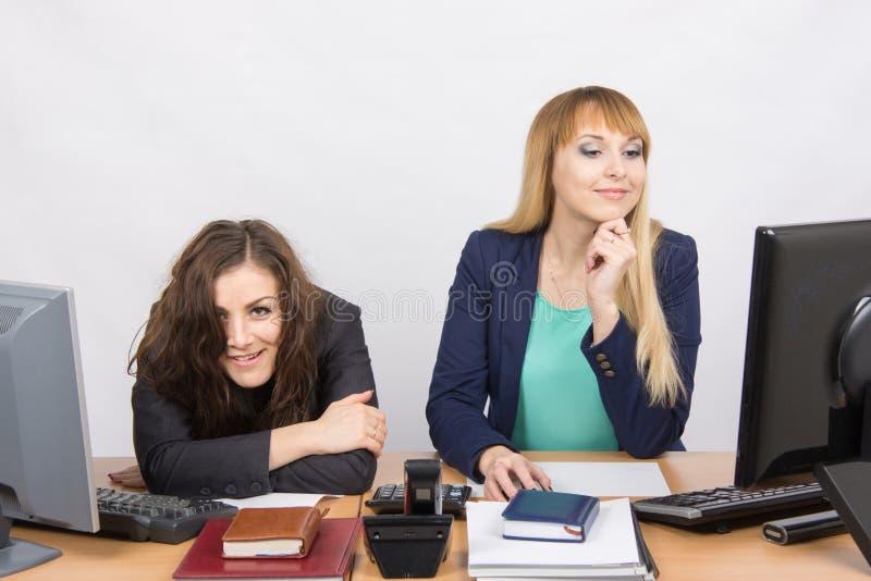 Läget i kontoret - galna blickar för en flicka i bilden, hennes kollega som ser bildskärmen royaltyfria foton