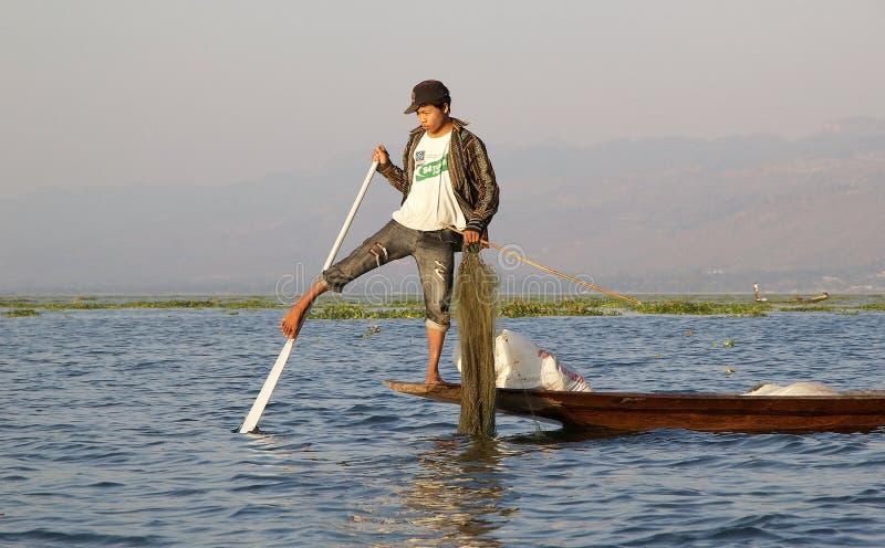 Lägga benen på ryggen rodden och fiske på sjön Inle Myanmar royaltyfria bilder