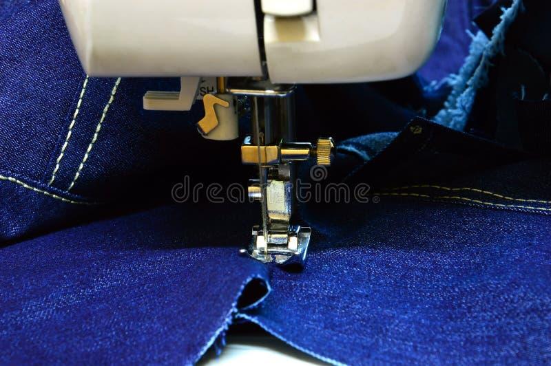 Lägga en mjuk stygn på denim på en symaskin Teknik för textilbearbetning Sättning hemma Makro, läge royaltyfria bilder