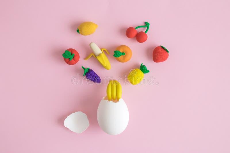Lägga framlänges av det vita ägget och frukter som är abstrakta på pastellfärgad rosa bakgrund arkivbilder