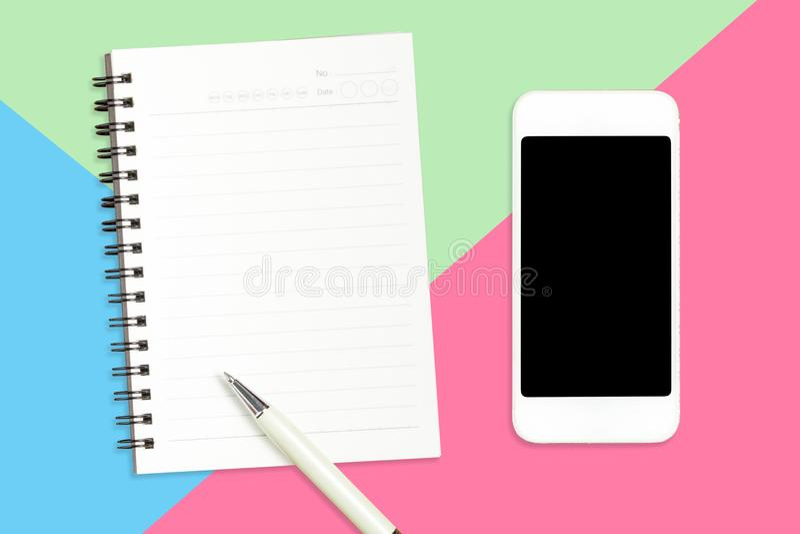 Lägga framlänges av Smartphone, den tomma anteckningsboken och den vita pennan på blå pastellfärgad färg, grön rosa pappersbakgru arkivbild