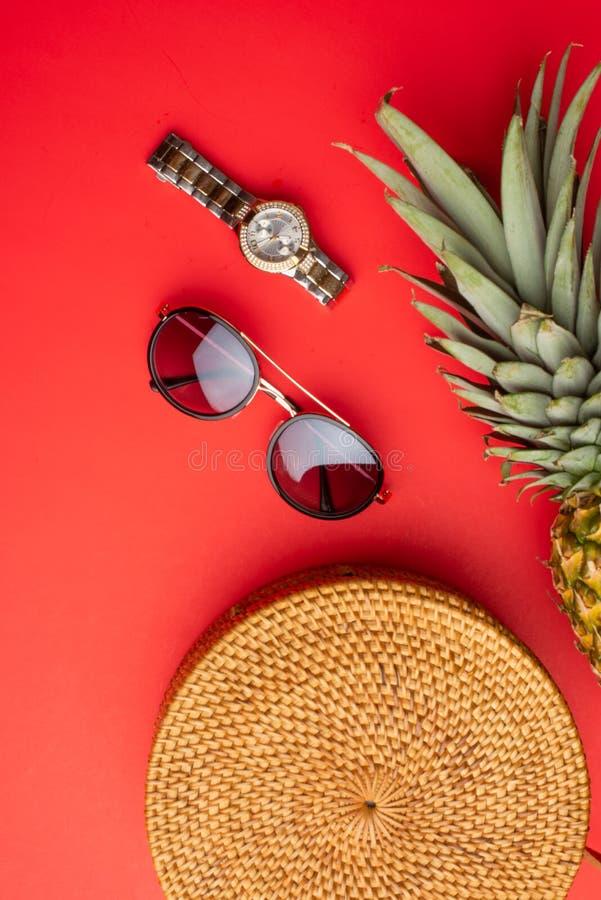 Lägga framlänges, den vide- modepåsen, solglasögon, tropisk ananas och dyra klockor och kvinnors mode för skosommar, begreppet arkivfoton