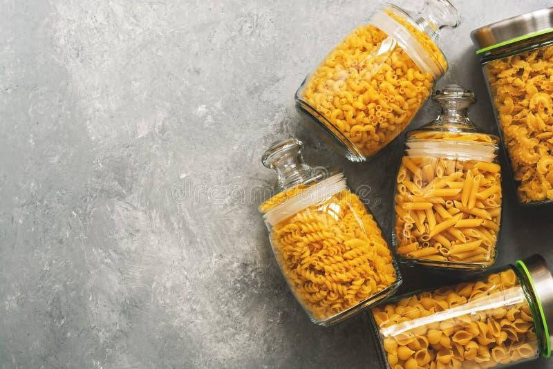 Lägga framlänges olik okokt pasta i en exponeringsglaskrus på en grå bakgrund Kopieringsutrymme, bästa sikt royaltyfria foton
