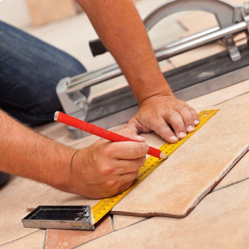 Lägga keramiska golvtegelplattor - mannen räcker markeringstegelplatta som ska klipps, c arkivfoton