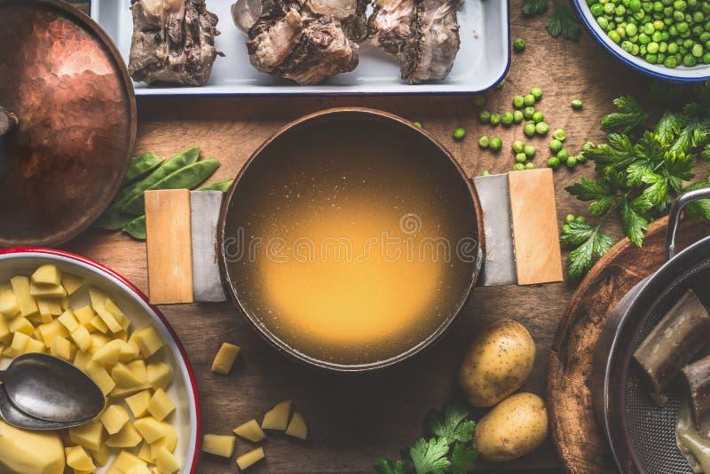 Lägga in med köttbuljong som lagar mat förberedelsen för potatissoppa med gröna ärtor royaltyfria bilder