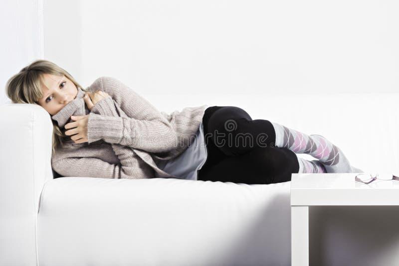 Lägga ner på en vit soffa arkivfoto