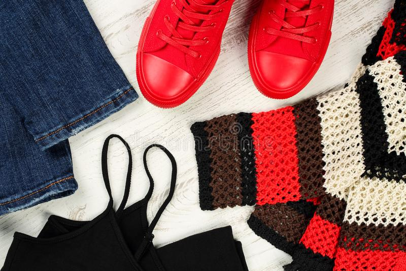 Lägga upp framlänges av tillfälligt detaljer för bekläda för kvinnor - jeans, röda gymnastikskor, svart sleeveless ärmlös tröja o arkivfoto