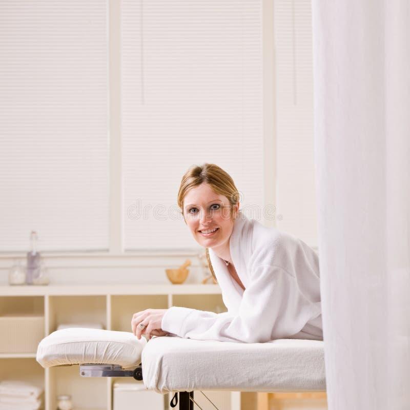 läggande av den väntande kvinnan för massagetabell arkivbilder