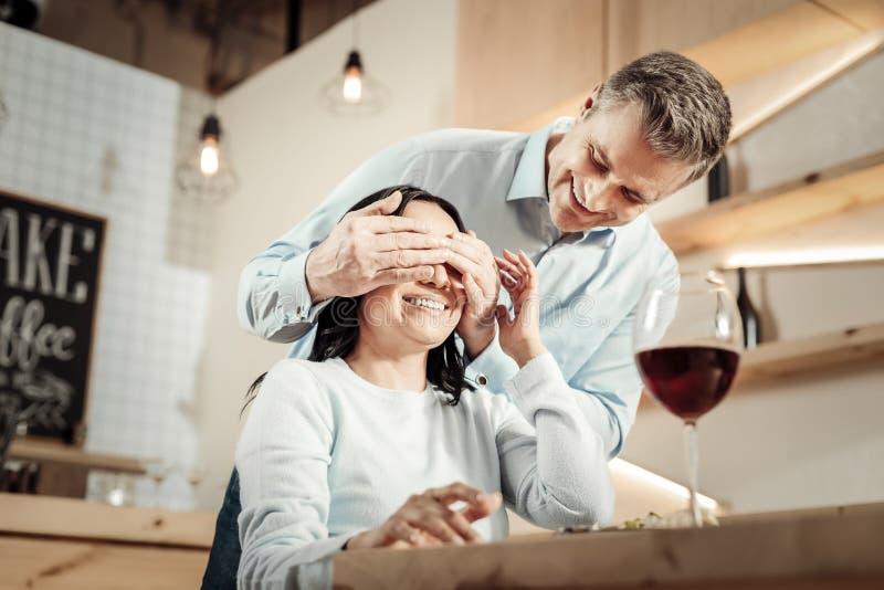 Läggande på man som täcker hans kvinnas ögon vid händer arkivfoton