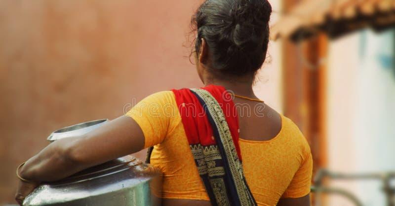 Lägger in bärande vatten för den fattiga bykvinnan i södra Indien royaltyfria foton