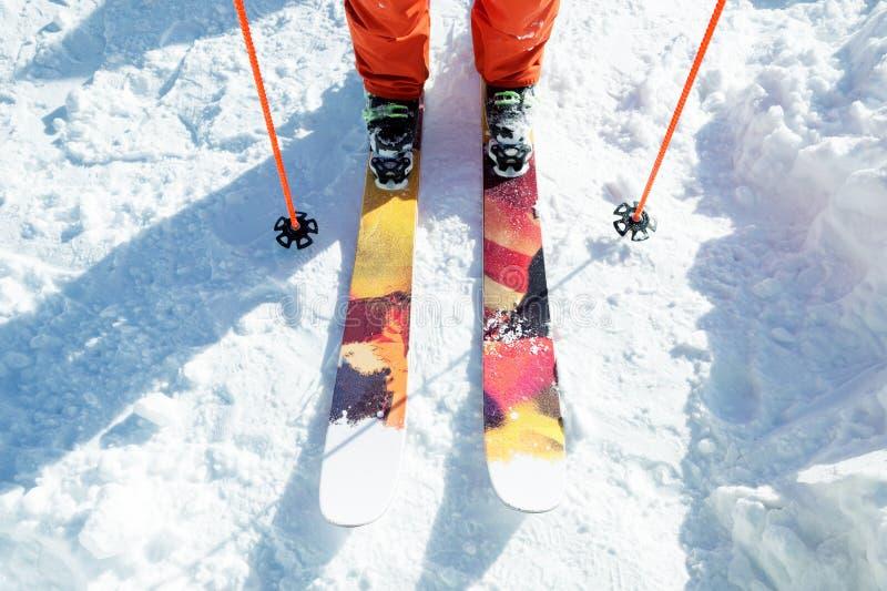 Lägger benen på ryggen idrottsman nenskidåkaren i en orange overall på en sportskidåkning på snö på en solig dag Begreppet av vin arkivbild