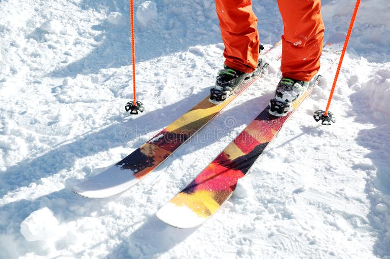 Lägger benen på ryggen idrottsman nenskidåkaren i en orange overall på en sportskidåkning på snö på en solig dag Begreppet av vin arkivfoton