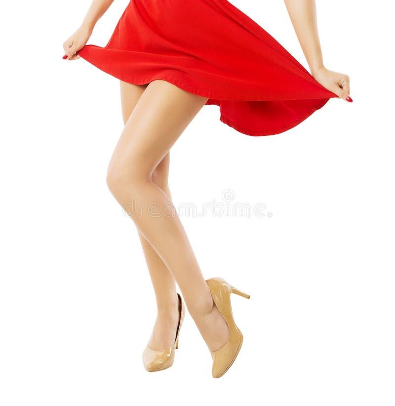 Lägger benen på ryggen kvinnadans i röd klänning över vit arkivfoto