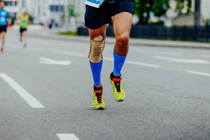 Lägger benen på ryggen löparemän i kompressionskalvmuffar royaltyfria bilder