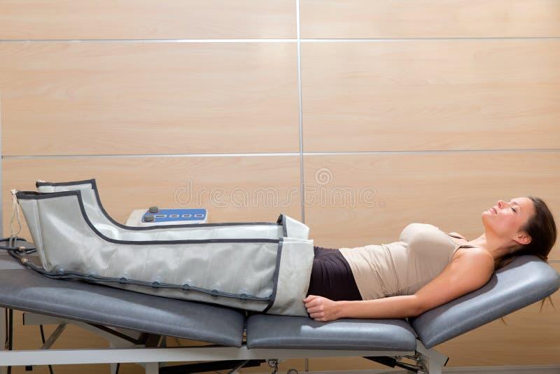 Lägger benen på ryggen pressotherapy bearbetar med maskin på kvinnan som är tålmodig i sjukhus fotografering för bildbyråer