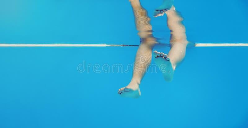 Lägger benen på ryggen undervattens- i simbassängen arkivbild
