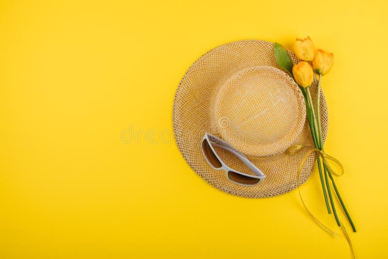 Lägger den kvinnliga modelägenheten för sommar med kopieringsutrymme Strandtillbehör, sugrörhatt, vit solglasögon och gula tulpan royaltyfria bilder