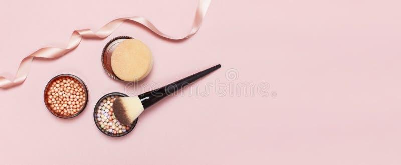 Lägger den pärlemorfärg rodnaden för boll, framsidapulver, makeupborsten och det rosa bandet på en pastellfärgad rosa lägenhet fö royaltyfri fotografi