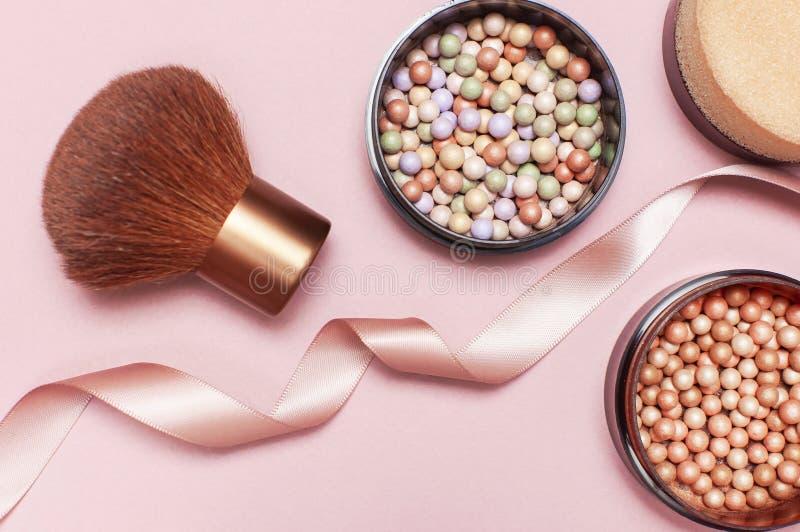 Lägger den pärlemorfärg rodnaden för boll, framsidapulver, makeupborsten och det rosa bandet på en pastellfärgad rosa lägenhet fö royaltyfria foton