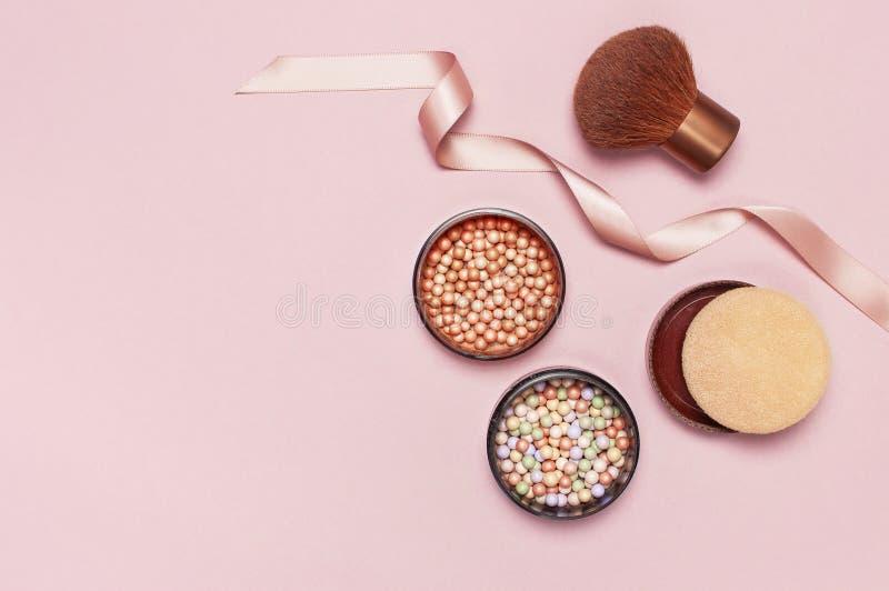 Lägger den pärlemorfärg rodnaden för boll, framsidapulver, makeupborsten och det rosa bandet på en pastellfärgad rosa lägenhet fö arkivfoton