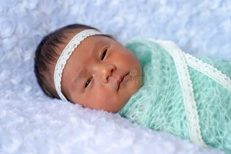 Lägger den sömniga framsidan Ovely för den nyfödda flickan ner på den vita filten warpping upp med ljust - grönt tyg, 6 dagar royaltyfri foto