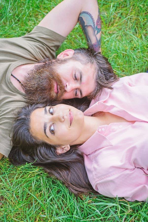 Lägger förälskat avslappnande för par på ängen Naturen fyller dem friskhet och fred Lyckliga man och flicka för Hipster skäggig arkivfoto
