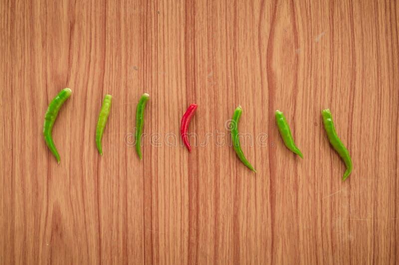 Lägger glödheta kryddiga thai peppar för en chili eller Mirchi bland den gröna chili som ordnas i en horisontalrad på träbakgrund arkivfoto