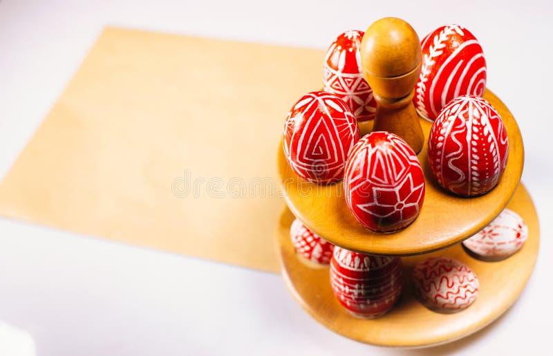 Lägger röda ägg för Closeuppåsk med den folk vita modellen omkring på ställningen för ägg som står på gammalt av papper på vit ba royaltyfria bilder