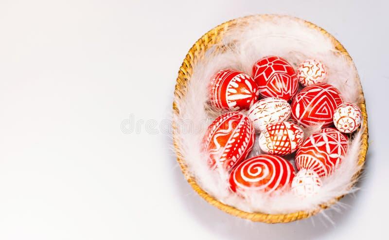 Lägger röda ägg för påsk med den folk vita modellen på fjäder in i korg på vit bakgrund, bästa sikt Ukrainska traditionella ägg fotografering för bildbyråer