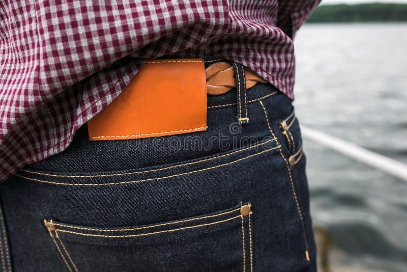 Lägre kropp av män, bakfickan av jeans och etiketten för en comercia royaltyfria bilder