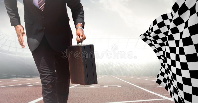 Lägre kropp för affärsman med portföljen på startlinjen på spår mot signalljus med den rutiga flaggan arkivfoto