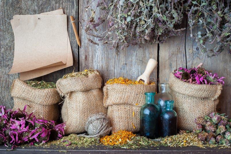 Läka örter i hessianspåsar, pappers- ark och flaskor arkivbilder