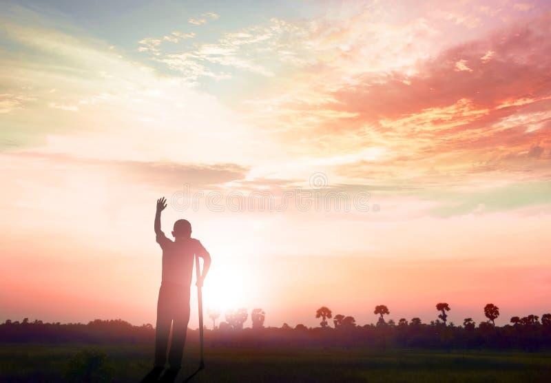 läka begrepp: Kontur en handikappade personerman som är stående upp på bergsolnedgångbakgrund arkivfoto