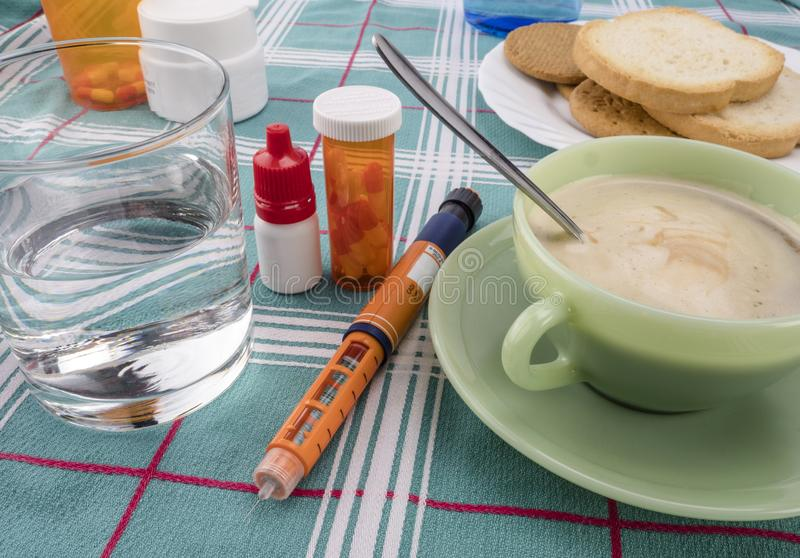 Läkarbehandling under frukosten, insprutningspump av insulin samman med en flaska av piller, begreppsmässig bild royaltyfri foto