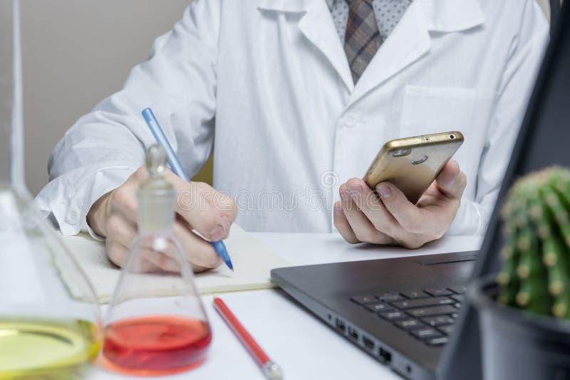 Läkare eller läkare som använder mobiltelefon i labbet, stäng royaltyfri foto