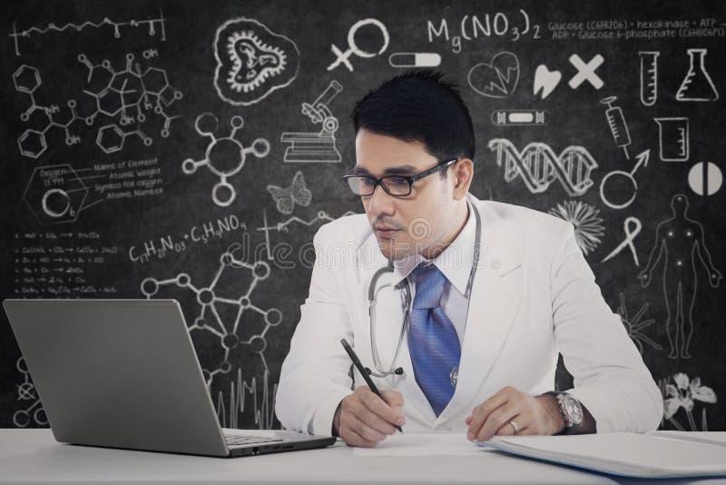 Läkare med bärbara datorn och klotter fotografering för bildbyråer