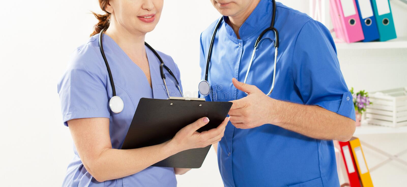 Läkare och sjuksköterska som diskuterar något på kliniken Två läkare på sjukvårdskontoret stänger bilden royaltyfri fotografi