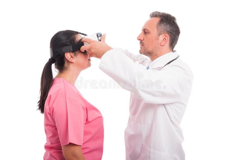 Läkare som justerar vrexponeringsglas på sjuksköterskahuvudet arkivfoto